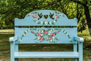 drewniana niebieska ławka z ludowym wzorem