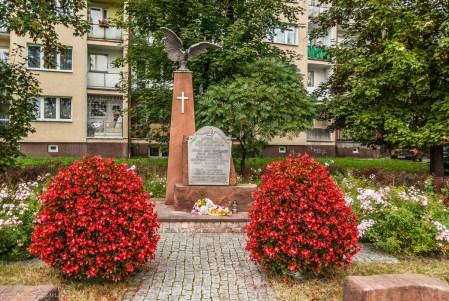 pomnik zwieńczony orłem w koronie na tle zieleni i bloków mieszkalnych