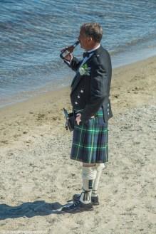 mężczyzna w spódnicy na plaży z piwem
