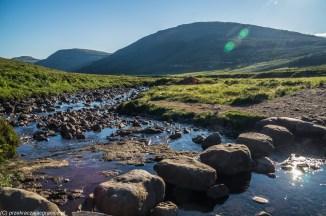 kamienie przecinające nurt rzeki w tle góry