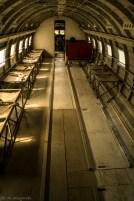 wnętrze starego samolotu z ławkami po bokach