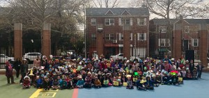 Other second grade students pose with their hats in the school yard