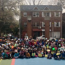 Second grade students pose with their hats in the school yard