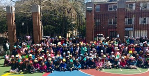 Group of Kindergarten students show off their hats in the school yard