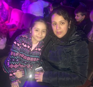 A parent and child sitting in the audience