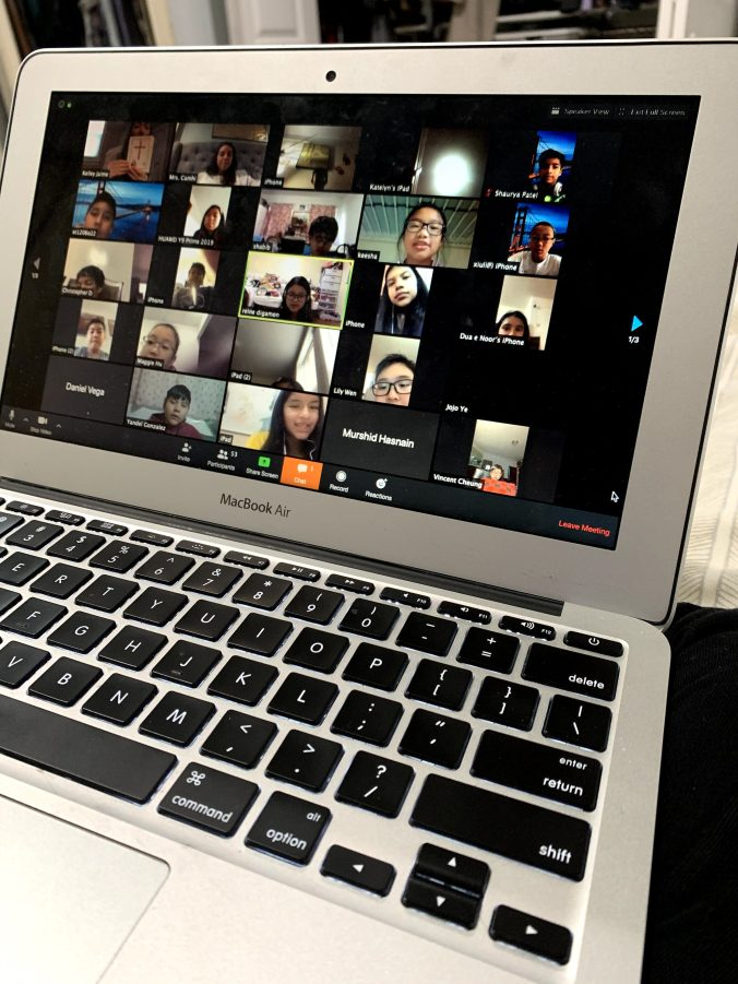A computer screen showing multiple faces of students in an online video session using Zoom