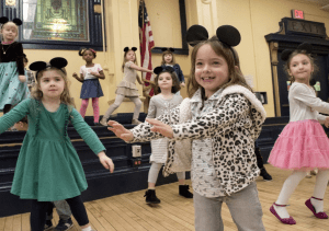 ps8 students smiling and dancing in unison in mouse ears