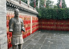 A decorative soldier stands watch in a courtyard. The walls are lined with good luck offerings.