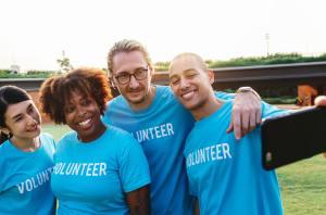 four people smiling wearing blue volunteer shirts