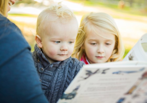 Mother Reading a Book to Her Two Adorable Blonde Children Wearing Winter Coats Outdoors.
