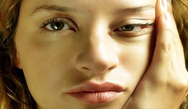 mulher-puxando_rosto_sindrome_fadiga_cronica