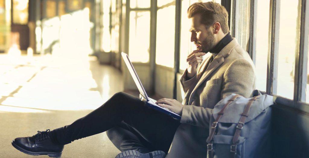 imagem mostra um rapaz de meia idade, sentado no chão, com um notebook no colo, atento ao atendimento de Orientação Psicológica Online que está acontecendo pela internet
