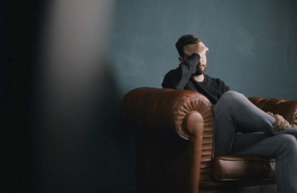 Homem sentado pensando.