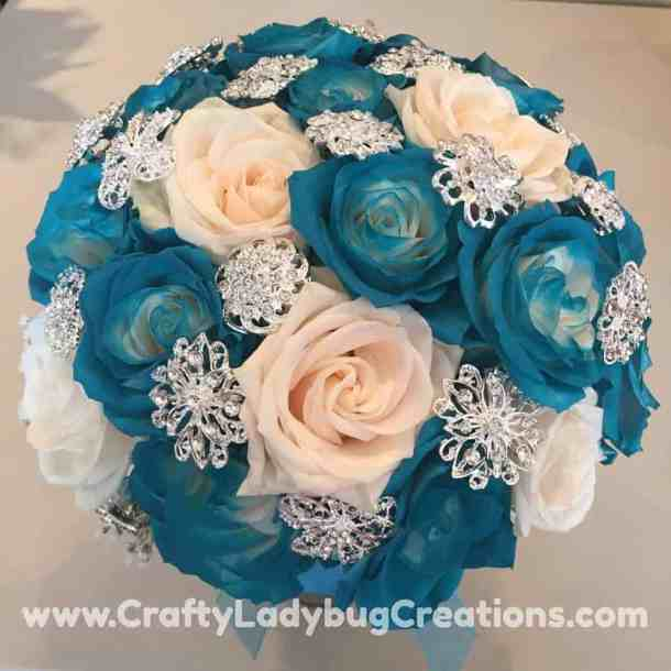 Malibu Blue and silver bridal bouquet with blue and white roses and rhinestone brooches. Our First Christmas Together Ornament - Using a wooden ornament, paint, rhinestones, Wink of Stella, and the Cricut Explore, I made a beautiful Christmas ornament for my daughter and son-in-law's first Christmas together. I used rhinestone brooches that were in my daughter's bridal bouquet to make this keepsake that they will cherish forever.