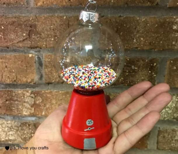 Make a Gumball Machine Christmas ornament using a flower pot, glass ball, red paint, sprinkles, and glue.