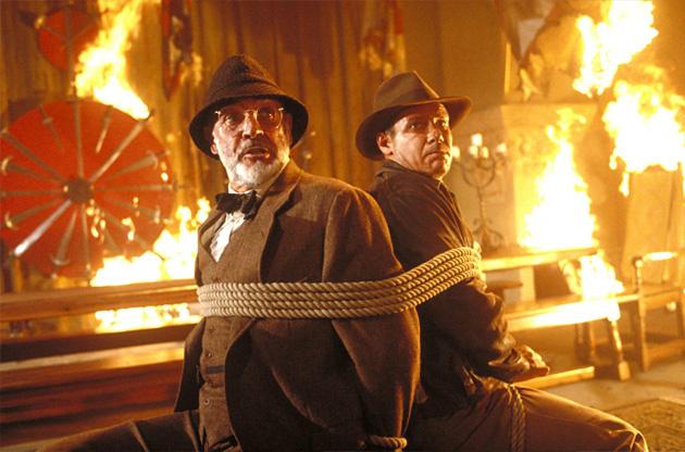 Imagen de un padre y su hijo atados atrapados en el fuego. Es una escena de la película Indiana Jones con Harrison Ford.
