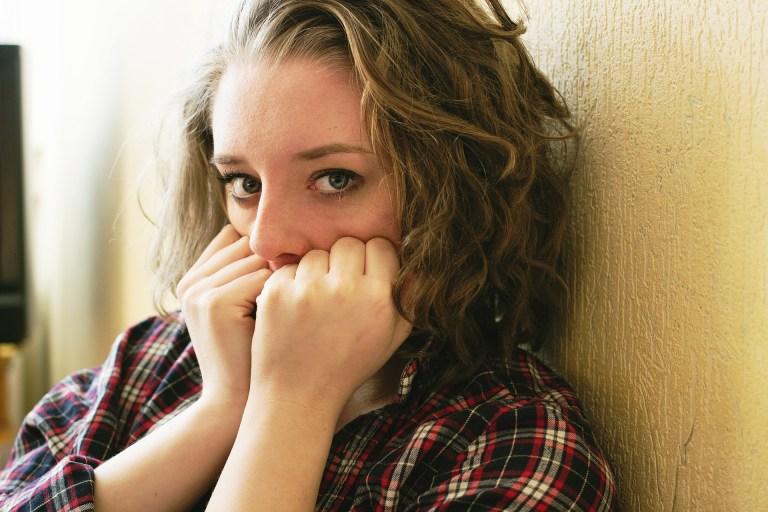 Foto de chica mirando la cámara con las manos que cubren la boca como signo de miedo.