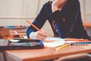 Foto de un chico en estado de ansiedad sentado en un banco con un lápiz en la mano mientras realiza los deberes.