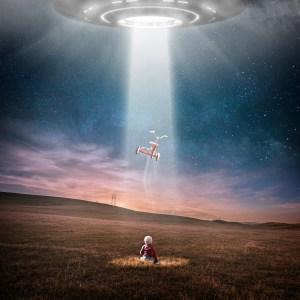 Ovni que proyecta una luz hacia el suelo donde está un niño con su triciclo.