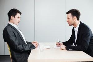 Fotografía de des hombres hablando el uno de frente al otro con una mesa en el medio