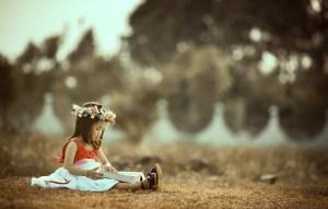 Niña leyendo un libro sentada en un parque