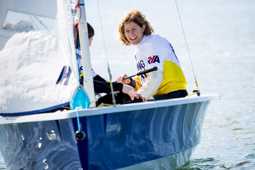 Woman sailing a dinghy for the first time and loving it