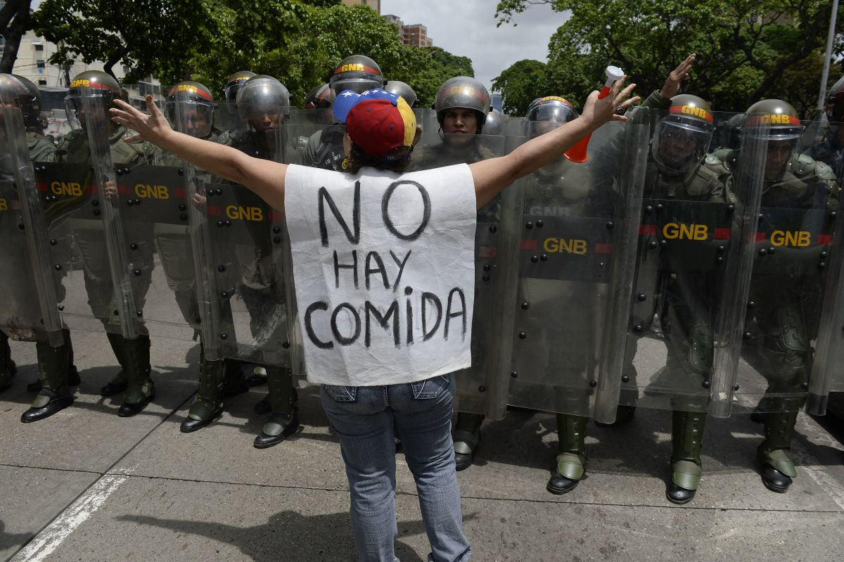 """A woman with a sign reading """"There is no food"""" protests against new emergency powers decreed this week by President Nicolas Maduro in front of a line of policemen in Caracas on May 18th, 2016."""