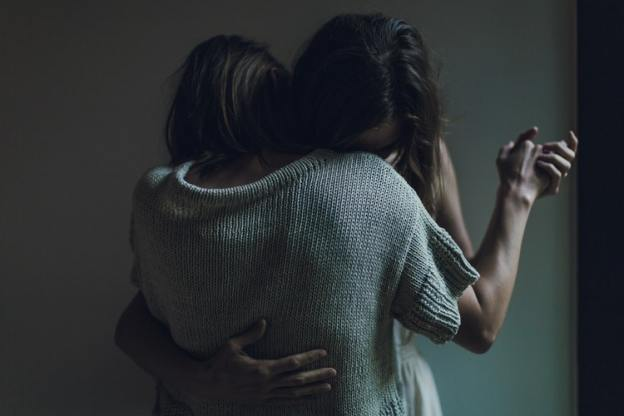 two people embrace in ballroom hold leaning their heads on each others shoulders.