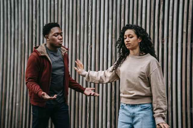 expressive multiethnic couple having conflict on street