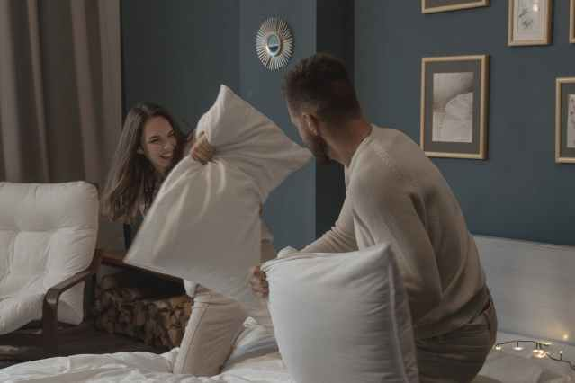 a couple having fun playing pillow fight