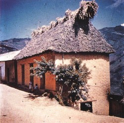 """House where mushroom sessions took place is built of adobe, has thatch """"dog-ears"""" over gable ends. Door, lower right, leads into ceremonial room."""