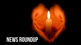 Hands clasped in heart shape around single lit candle