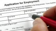 A hand with a pen filling out an application for employment