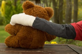 Kind mit Gipsarm und Teddy