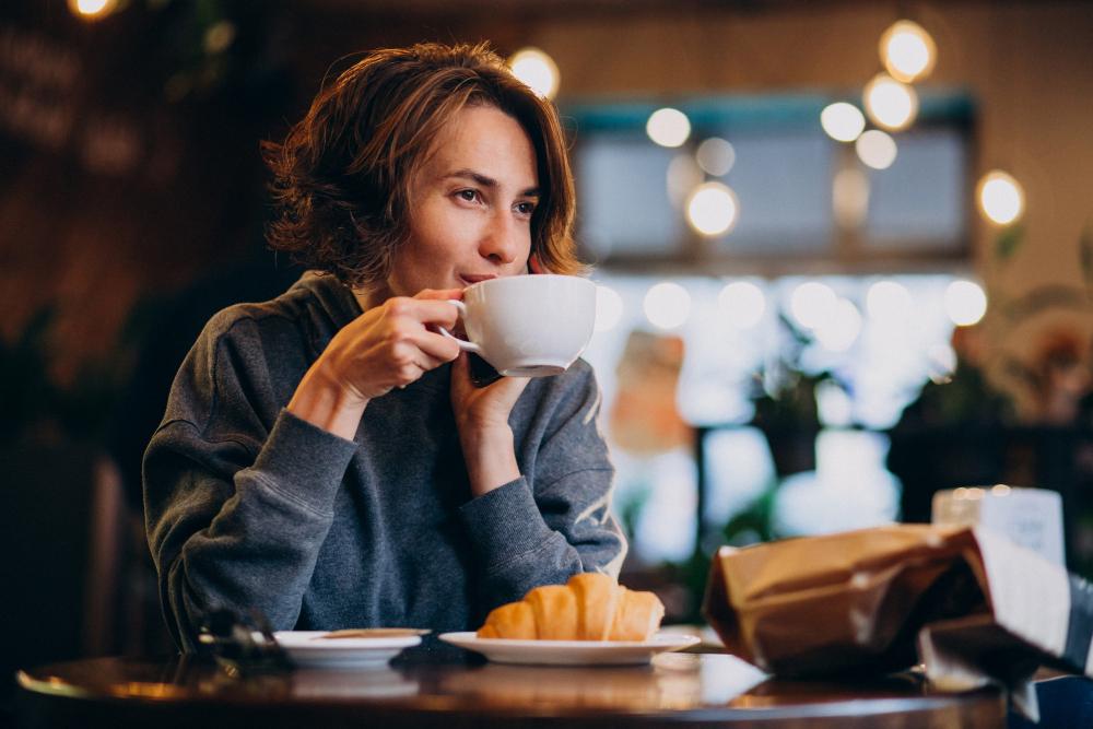 joven mujer tomando café con croissants