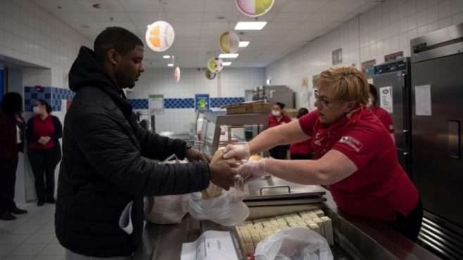 Phillip Jackson, military spouse, receives grab-and-go meals from Sonja Gates, Department of Defense Education Activity school meal program manager at Ramstein Air Base, Germany, March 25, 2020, as children attended school from home. (Airman 1st Class Jennifer Gonzales/Air Force)