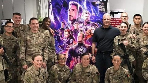 Troops in Afghanistan pose in front of an Avengers poster before a free screening of the blockbuster movie.