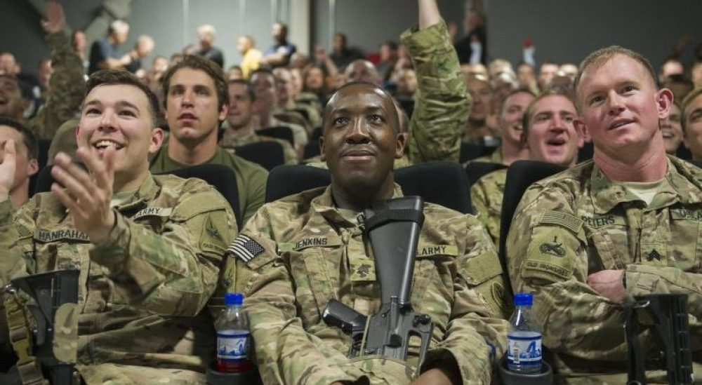 """Service members deployed to Bagram Air Field, Afghanistan, clap and cheer as they prepare to view first showing of """"Star Wars: The Force Awakens,"""" here, Dec. 22, 2015. The Army & Air Force Exchange Service partnered with Walt Disney Studios to give service members a chance to see the movie in a deployed location. (U.S. Air Force photo by Tech. Sgt. Robert Cloys)"""