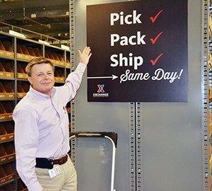 "Dave Nelson gestures at ""Pick, Pack, Ship - Same Day!"" sign"