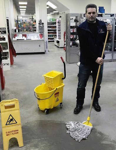 Camp Bondsteel Sales Associate Daut Murtezi quickly reacts to a spill and uses appropriate signage to ensure customers and associates at the store in Kosovo are aware of the hazard.