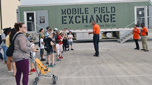 Former Main Store Manager Neal Smart, center, show children and their parents the MFE the Exchange uses to serve deployed Warfighters. Smart is joined by associates Betty Pyka and Cleveland Sykes. (Smart recently became store manager at RAF Lakenheath in England).