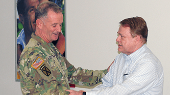 Fort Drum General Manager James Osborne, right, shakes hands with Division Commander Maj. Gen. Walter Piatt. The commander stopped by the Exchange to thank Osborne for his service to the Soldiers.