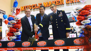 Fort Sill Exchange general manager Don Walter Jr.; Mike Roper, Muscle Maker Grill CEO; and Maj. Gen. Wilson A. Shoffner, Fort Sill commanding general, cut the ribbon to open Muscle Maker Grill Nov. 21.