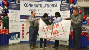 Exchange shopper Anita Armstrong, second from left, and General Manager Vanessa Rowland take scissors to Armstrong's MILITARY STAR bill, which the Exchange Credit Program paid in full during a sweepstakes. Joining are, far left, are Armstrong's husband, retired Tech Sgt. Michael Armstrong; and, far right, Exchange Vice President, Credit Operations, Tommy Ward.