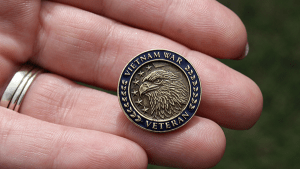 Vietnam Veteran lapel pin in hand.