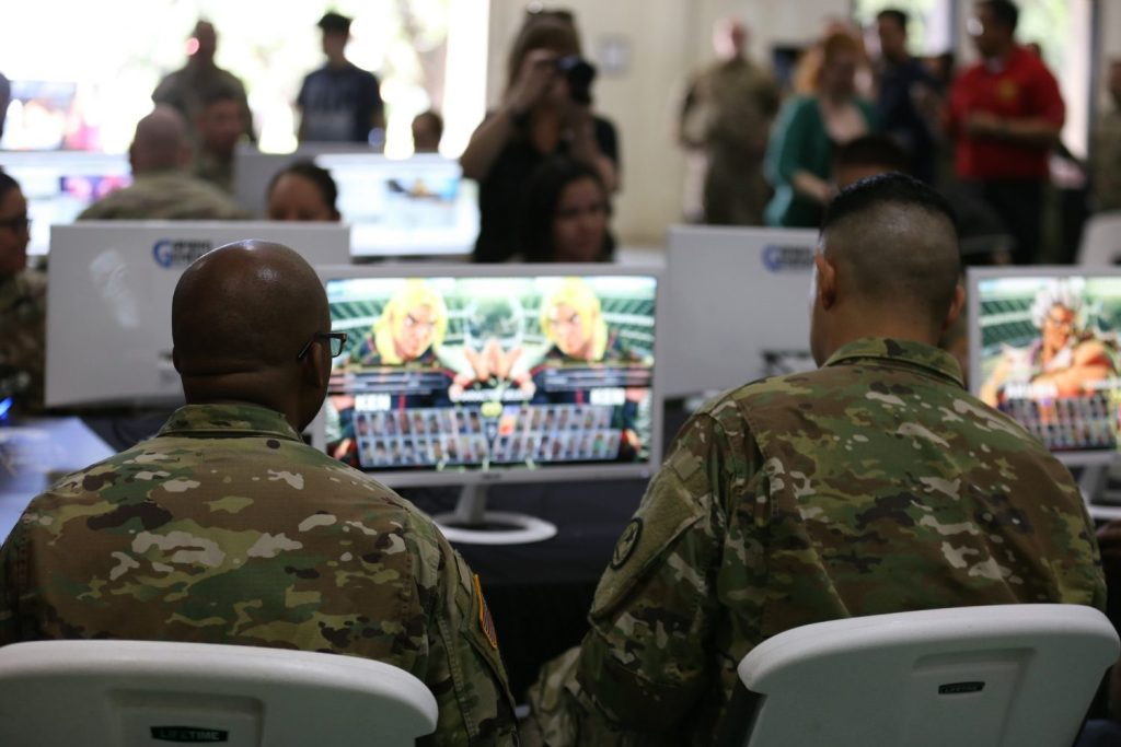 Two Soldiers play a video game on a large screen.