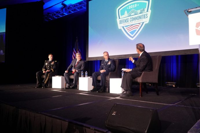 Military and Exchange leaders sit on a stage discussing modern campus dining