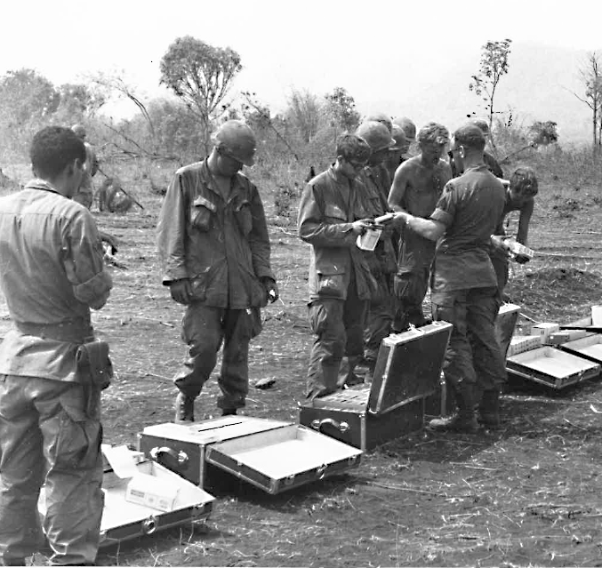 Soldiers during the Vietnam War look through cases full of Exchange supplies brought to them by either truck or chopper, 1967.