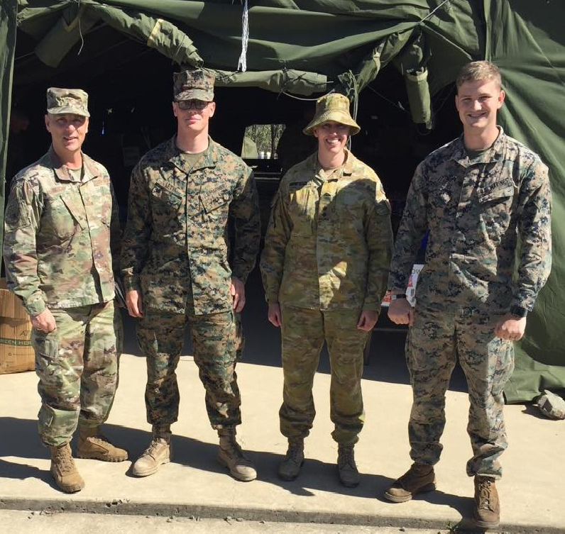 Exchange Pacific Region Commander Col Scott Maskery, left, meets with Australian Army LTC Benefield, second from right, Camp Commandant, Camp Growl, Shoalwater Bay Military Training Area, about the mobile field exchange's operations and capabilities. They are joined by U.S. Marines LCPL Julian Leyva, second from left, and SGT Chad Elders, right.