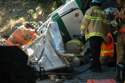 When a tractor trailer truck drove off of an elevated overpass and crashed onto the road below, the driver was trapped. King County medics crawled into the wreckage to begin emergency medical care inside of the cab while other crews worked on cutting him out of the mangled metal of the truck.
